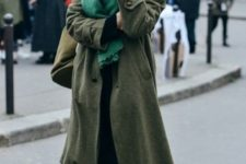 With olive green midi coat, black pants and brown leather shoes