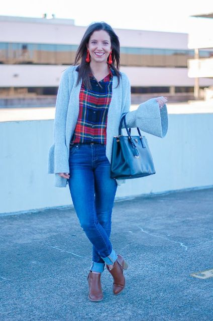With plaid button down shirt, cuffed jeans, brown ankle boots and black bag