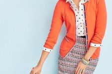 With polka dot button down shirt, printed tweed pencil skirt and orange clutch