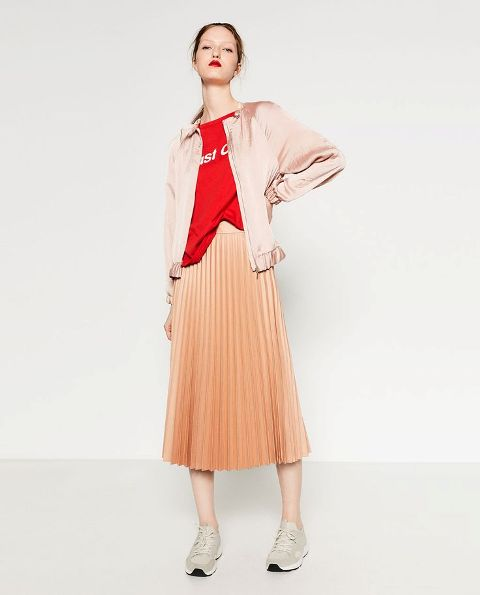 With red labeled t-shirt, peach colored pleated midi skirt and sneakers
