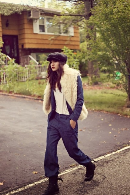 With white faux fur vest, navy blue blazer, navy blue loose pants, lace up flat boots and white t-shirt