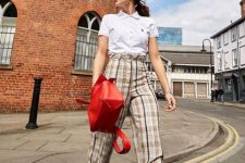 With white shirt, red leather bag and brown platform boots