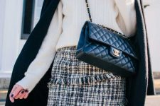 With white sweater, black coat and black leather bag