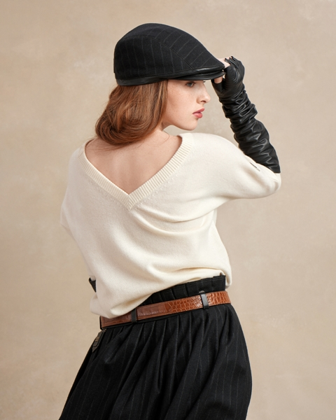 With white sweater, brown belt, black pleated skirt and gloves