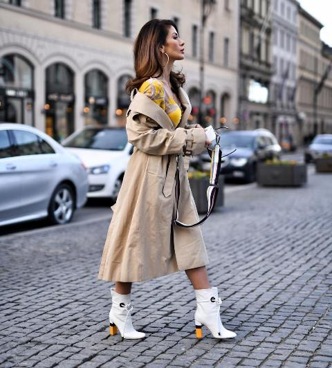 With yellow and beige dress, white bag and white boots