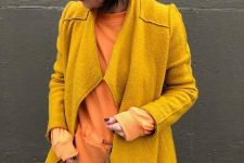 With yellow coat, navy blue jeans and orange shirt
