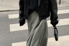 a black chunky knit sweater, a black leather jacket, an olive green skirt, blakc boots and a bag