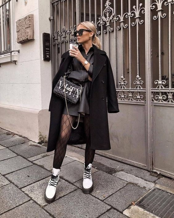 a black leather shirtdress, black tights, white combat boots, a black coat and a bag