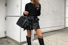 a black top, a black lacquer leather mini, black knee high boots and a comfortable bag