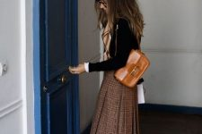 a black top, a brown plaid pleated midi, an amber bag and matching knee high boots