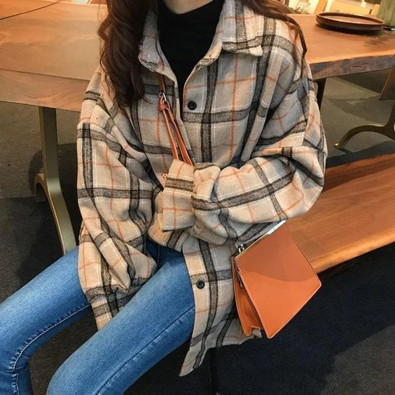 a black turtleneck, an oversized plaid flannel shirt and blue skinnies plus a classic amber bag