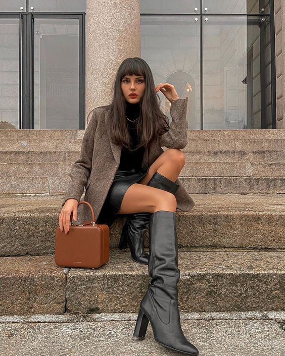 a black turtleneck and a black leather skirt plus boots, a brown woolen blazer, a chain and a brown bag