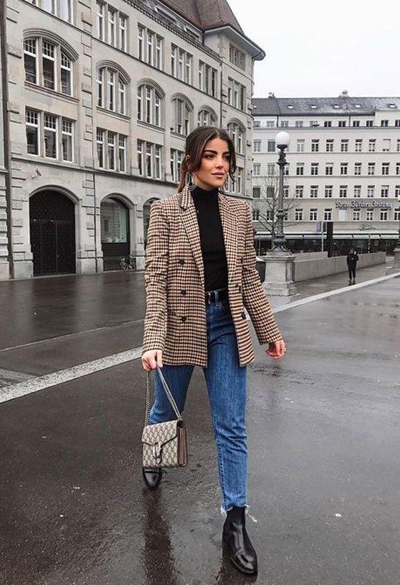 a black turtleneck, blue jeans, a plaid blazer and a printed bag plus black Chelsea boots
