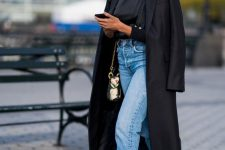 a black turtleneck, blue jeans, black heels, a trench and a whimsy bag for a statement