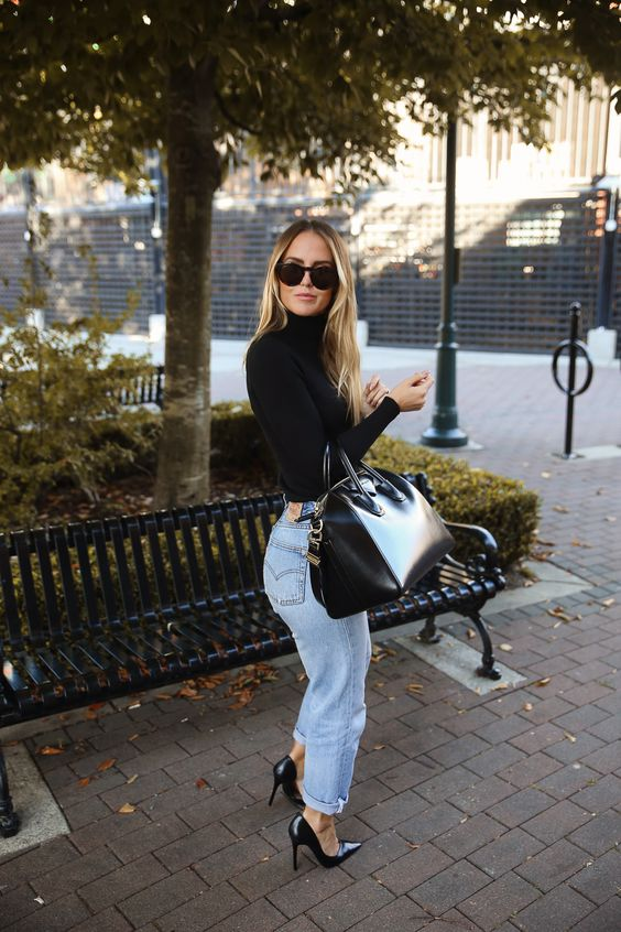 a black turtleneck, light blue slouchy jeans, black heels and a large bag for work