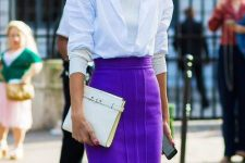 a bold work outfit with a creamy turtleneck, a white shirt, bold purple sheath skirt with a front slirt and a white clutch