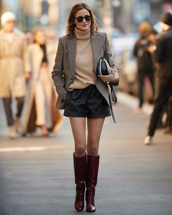 a camel turtleneck, black leather shorts, a plaid blazer, burgundy boots and a black bag