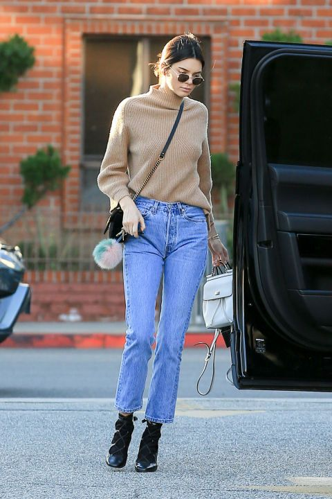 a camel turtleneck, blue cropped jeans, black lace up booties and a black bag