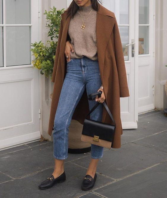 a camel turtleneck, blue cropped skinnies, black moccasins, a two tone bag and a brown coat