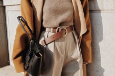 a camel turtleneck, white pants, a brown belt, a mustard coat, a black bag for fall or winter