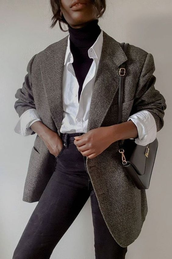a casual look with a black turtleneck, a white shirt, a grey oversized blazer, black jeans and a black bag