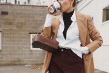 a casual work look with a black turtleneck, a white shirt, a tan blazer, burgundy pants and a brown bag