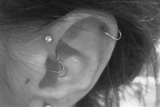 a daith, forward helix, upper helix and lobe piercing, with studs and heart-shaped earrings