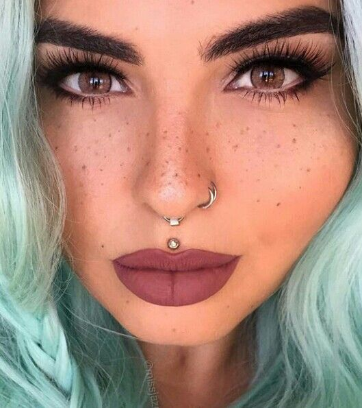 a double nose piercing with rings, a septum piercing with a ring and a medusa piercing with a stud