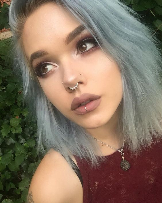 a double nose piercing with studs, a septum piercing with an embellished ring and a vertical lip piercing