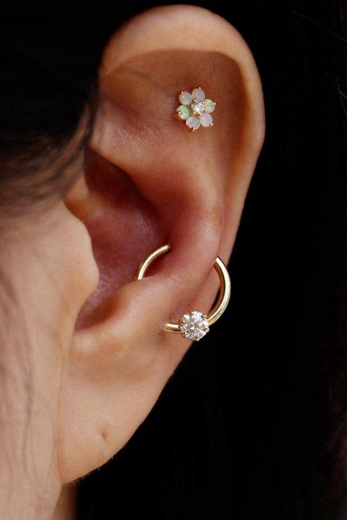 a flat piercing with a mother of pearl stud and a snug plus lobe piercing with a gold hoop with a diamond