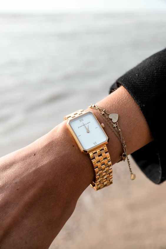 a gold bracelet watch plus a copper chain one with pendants for a relaxed and casual feel