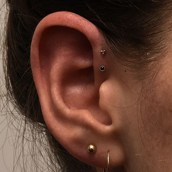 a gold stud and a hoop in the lobe and a gold and black stud in the forward helix