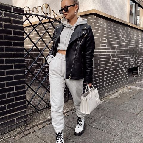 a grey cropped hoodie and joggers, white combat boots, a black leather jacket and a white bag
