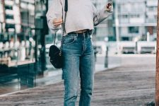 a grey cropped sweatshirt, blue cropped jeans, black sneakers and a black bag with chain