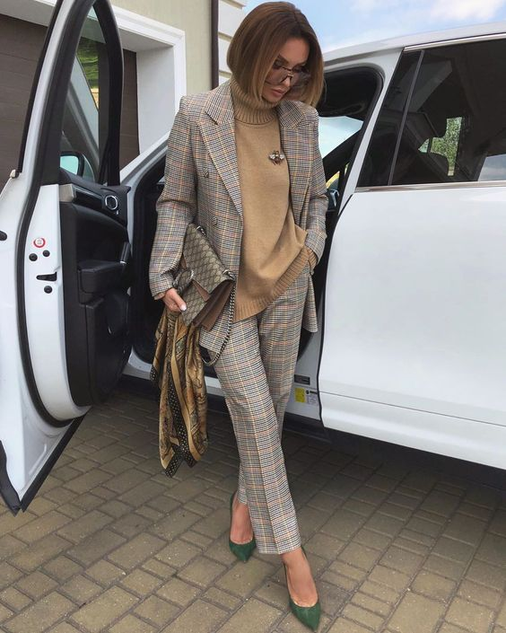 a grey plaid pantsuit, a camel turtleneck with a brooch, green shoes and a printed bag