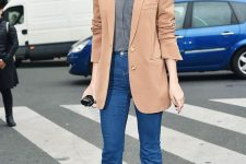 a grey tee, blue flare jeans, a tan oversized blazer and burgundy booties for a 70s inspired look