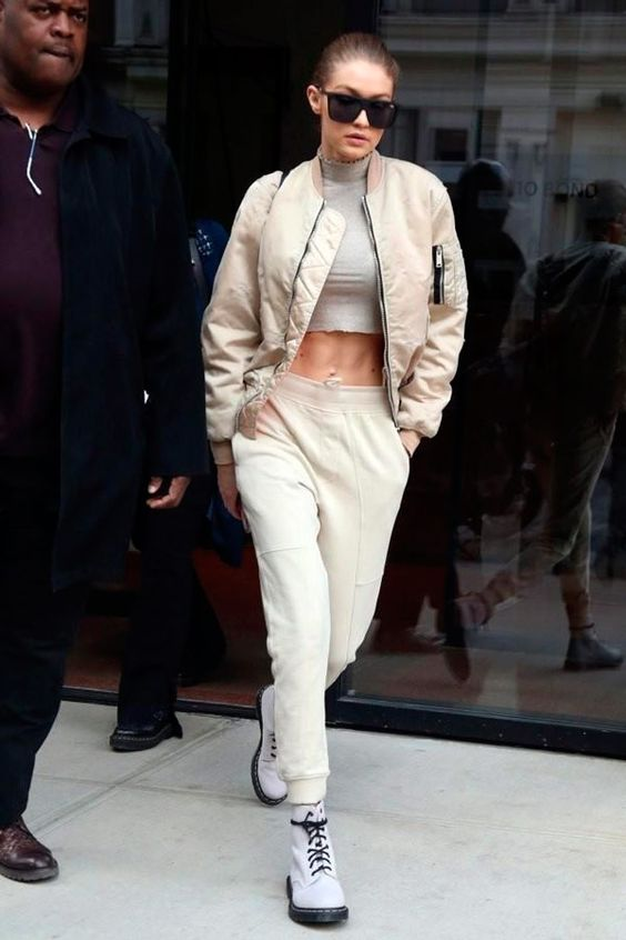 a grey turtleneck crop top, neutral joggers, white combat boots, a tan bomber jacket by Gigi Hadid