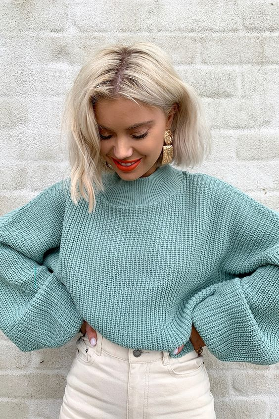 a light green cropped balloon sleeve sweater plus white jeans and statement earrings for the fall