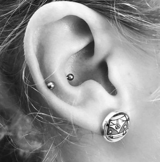 a lobe and a snug piercing with a statement earring look bold and very edgy