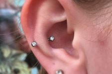 a lobe piercing and a snug piercing with matching silver and Swarovski crystals are chic