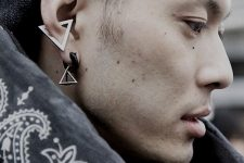 a lobe piercing done with a ring and triangle earring plus a statement triangle earring in the conch