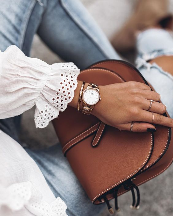 a mixed metal watch and a copper bracelet stacked plus rings finish off a soft girlish look