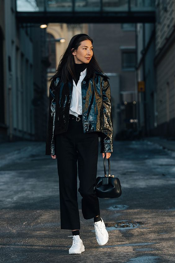 a monochromatic outfit with a black turtleneck, a white shirt, a black leather jacket, pants and a bag plus white trainers