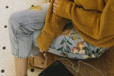 a mustard chunky knit sweater, blue floral embroidery denim, mustard mules and a black bag
