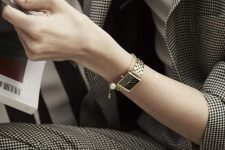 a plaid pantsuit and a white shirt for a work look finished with a gold bracelet watch and a chain bracelet with a pearl