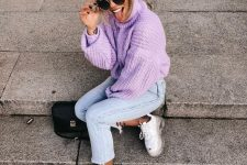 a purple chunky knit sweater with a turtleneck, blue cropped jeans and white trainers plus a black bag