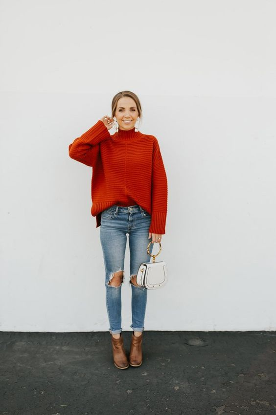 a red ribbed oversized turtleneck sweater, blue ripped jeans, brown booties and a white bag