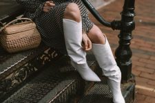 a romantic polka dot A-line midi dress, white knee high boots and a quirky woven bag