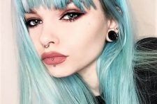 a septum piercing with a ring, a vertical labret piercing, tunnel piercing and blue hair