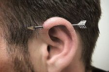 a simple horizontal industrial piercing with an arrow barbell is always a catchy idea